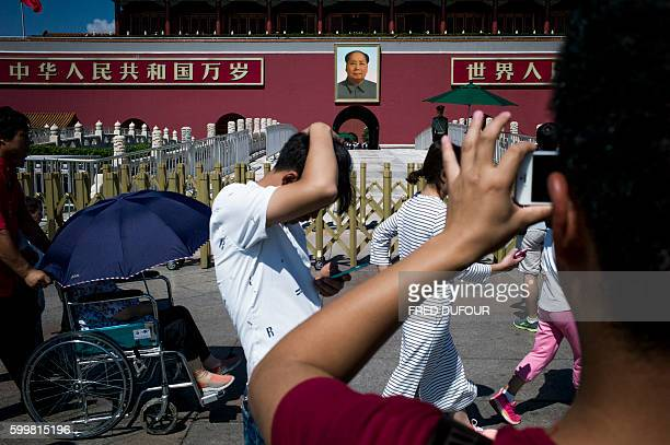 This picture taken on September 5 2016 shows tourists pose in front of a giant portrait of Mao Zedong at the gate of the Forbidden City in Beijing...