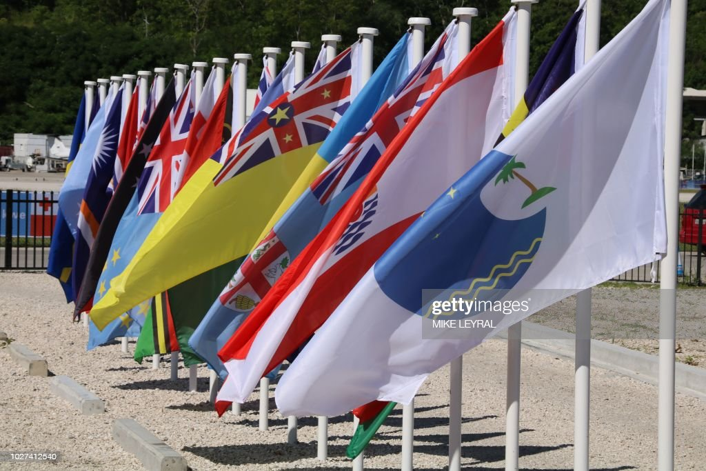 This picture taken on September 5, 2018 shows flags from the Pacific Islands countries being displayed in Yaren on the last day of the Pacific Islands Forum (PIF). - PIF members on September 5 signed a security agreement promoting cooperation on issues such as trans-national crime, illegal fishing and cyber-crime.The agreement, called the Boe Declaration, also recognised the need for joint action on 'non-traditional' threats, primarily climate change.