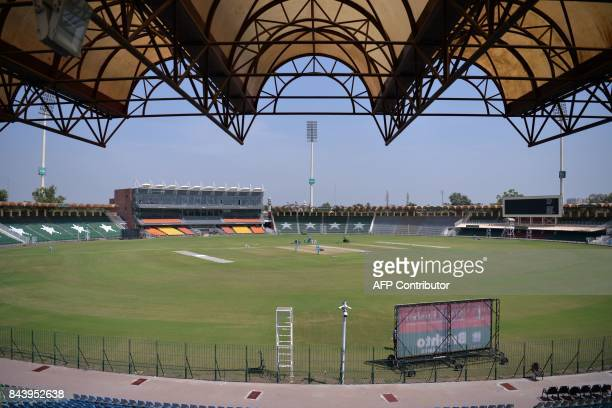 This picture taken on September 7, 2017 shows ground staff preparing the cricket pitch of the Gaddafi Stadium in Lahore. Groundsmen are rolling down...
