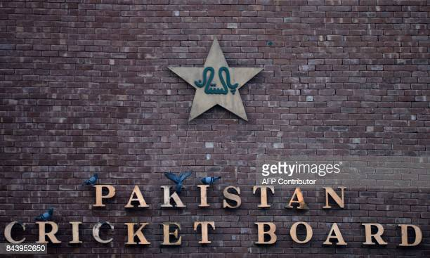 This picture taken on September 7, 2017 shows pigeons resting on a sign for the Pakistan Cricket Board at the Gaddafi Stadium in Lahore. Groundsmen...