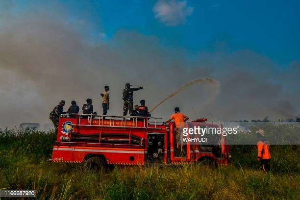 This picture taken on September 7 2019 shows Indonesian firefighters battling a fire at a palm oil plantation in Pekanbaru Riau Indonesian...