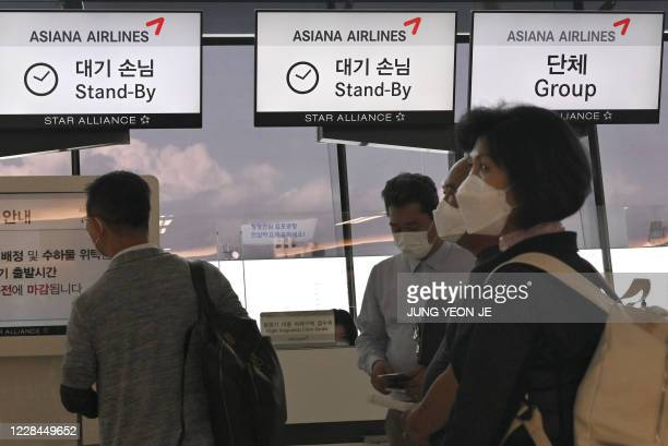 This picture taken on September 8 2020 shows passengers waiting in line in front of a checkin counter of Asiana Airlines at Gimpo airport in Seoul A...