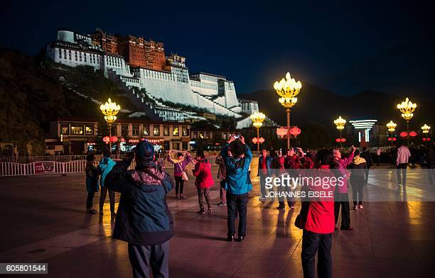 This picture taken on September 9 2016 shows tourists in front of the iconic Potala Palace in the regional capital Lhasa in China's Tibet Autonomous...