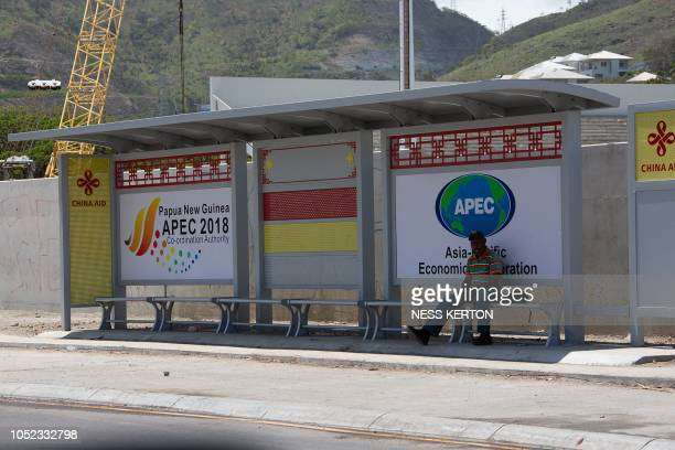 This picture taken on September 9 2018 shows a man sitting at a bus stop decorated with billboards for the upcoming AsiaPacific Economic Cooperation...