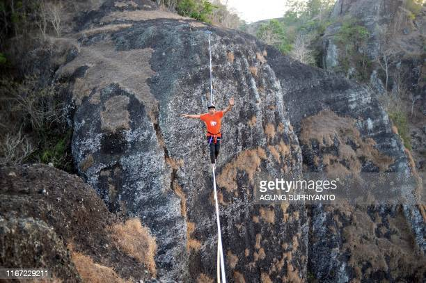 TOPSHOT This picture taken on September 9 2019 shows extreme sport athlete Andi Ardi walking on a tightrope at the height of 740 meters on Mount...