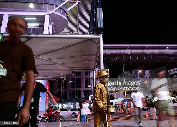 This picture taken September 21 2016 shows Malaysian street performer known as 'Goldman' posing on a street in the popular Bukit Bintang tourist spot...