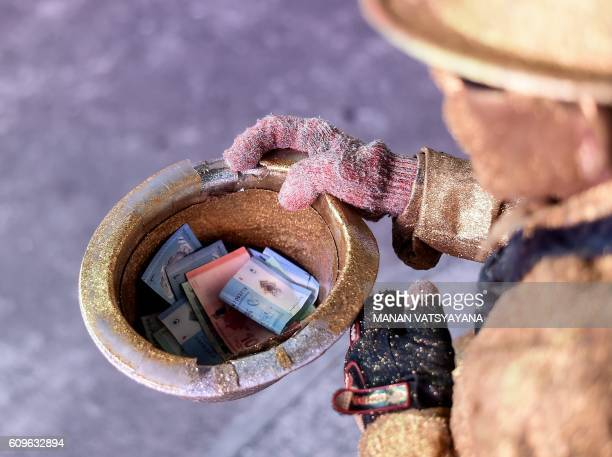 This picture taken September 21 2016 shows Malaysian street performer known as 'Goldman' holding his tophat filled with money on a street in the...