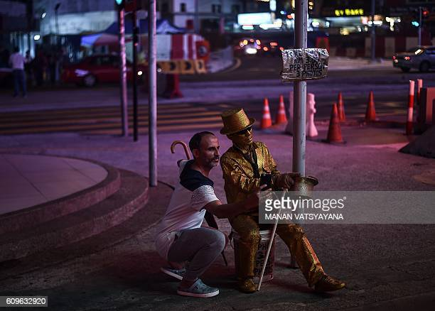 This picture taken September 21 2016 shows Malaysian street performer known as 'Goldman' posing with a tourist on a street in the popular Bukit...