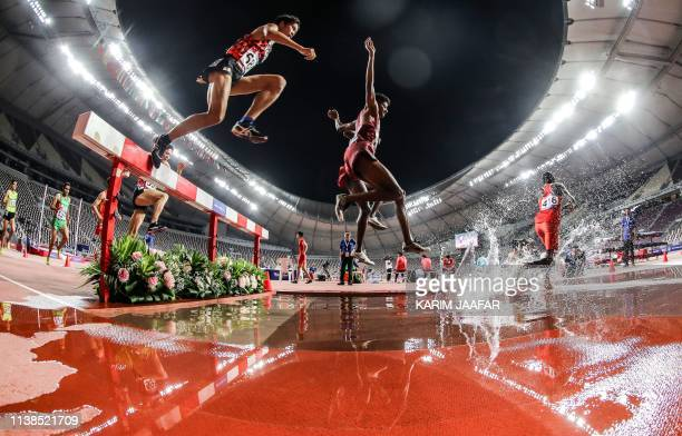 This picture taken with a fish-eye lens on April 21, 2019 shows athletes competing in the 3000m men's steeplechase race during 23rd Asian Athletics...