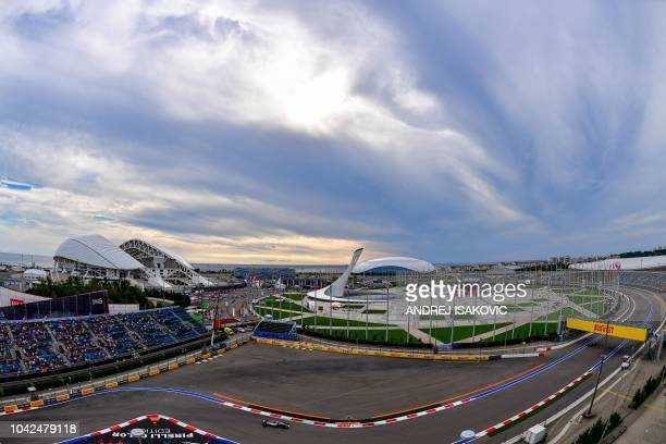 This picture taken with a fisheye lens shows Mercedes' British driver Lewis Hamilton steering his car during the second practice session of the...