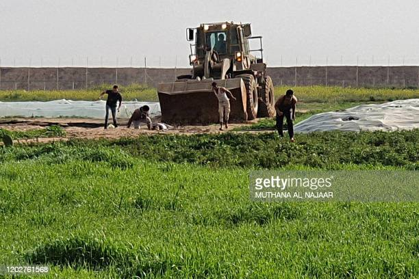 TOPSHOT This picture taken with a mobile phone on February 23 2020 shows men trying to collect a body as a bulldozer approaches them along the...