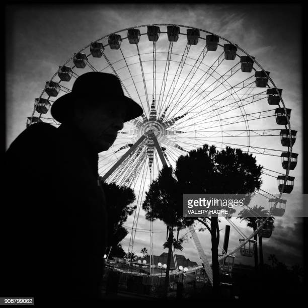 This picture taken with a mobile phone shows a man walking in front of the Ferris wheel in the French riviera city of Nice on January 22 2018 / AFP...
