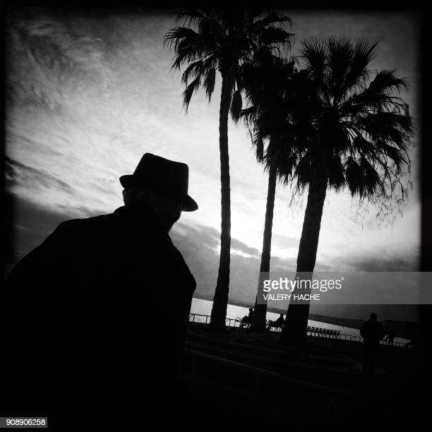 This picture taken with a mobile phone shows a man walking past palm trees on the 'Promenade des anglais' in the French riviera city of Nice on...