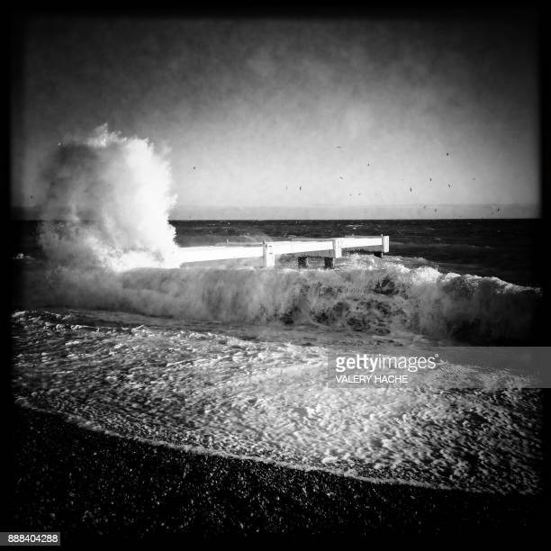 This picture taken with a mobile phone shows a wave washing ashore on the beach of the Promenade des Anglais on the French riviera city of Nice on...