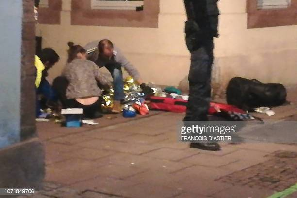 TOPSHOT This picture taken with a mobile phone shows rescuers treating an injured person in the streets of Strasbourg eastern France after a shooting...