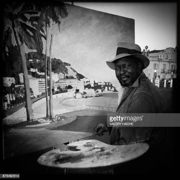 This picture taken with a mobile phone shows South Sudanese born Spanish artist Omar Logang posing in front of his painting on the Promenade des...