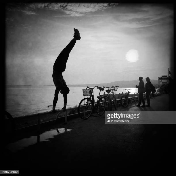 This picture taken with a mobilephone shows a person performing acrobatics on the 'Promenade des Anglais' on the french riviera city of Nice on...