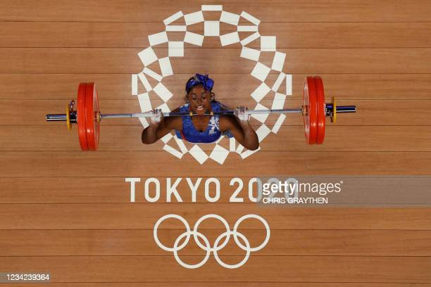 This picture taken with a robotic camera shows Cuba's Marina de la Caridad Rodriguez Mitjan competing in the women's 64kg weightlifting competition...