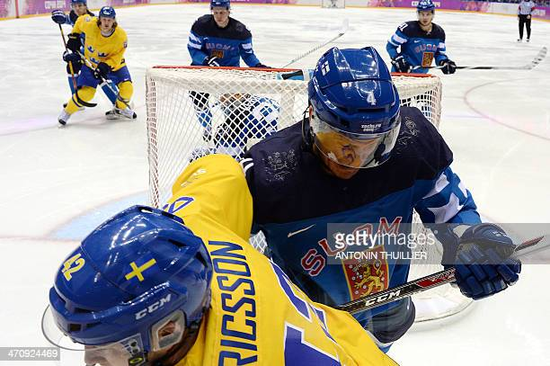 This picture taken with a robotic camera shows Sweden's Jimmie Ericsson vying with Finland's Ossi Vaananen during the Men's Ice Hockey Semifinal...
