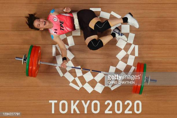 This picture taken with a robotic camera shows Taiwan's Kuo Hsing-chun reacting after winning the gold medal in the women's 59kg weightlifting...