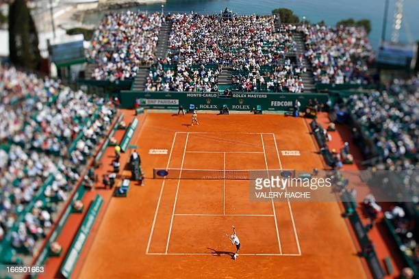 This picture taken with a tilt and shift lens shows Serbia's Novak Djokovic serving to Argentina's Juan Monaco during their MonteCarlo ATP Masters...