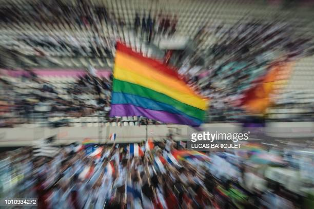 This picture taken with long time exposure shows participants of the French team holding a rainbow flag as they march onto the field during the...
