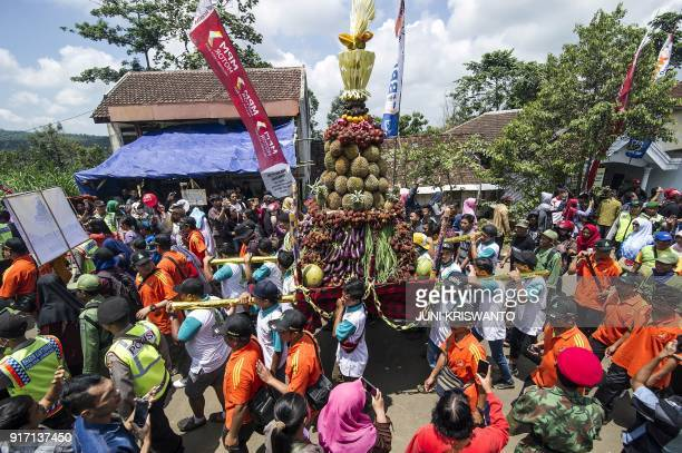 This picture was taken on February 11 2018 shows Indonesian men carrying an ornament of durian fruit during the Durian Festival locally called...