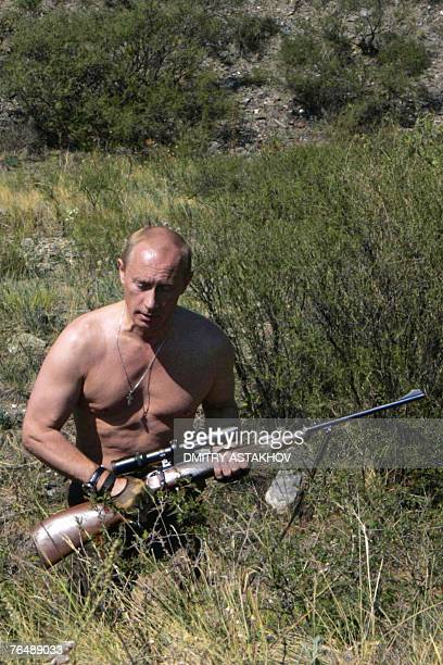 VERSION This pool picture provided 03 September 2007 shows Russian President Vladimir Putin carrying a hunting rifle in the Republic of Tuva 15...