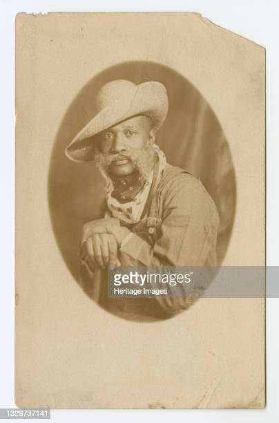 This real photo postcard features an image of a man in western attire. He is wearing a long sleeve shirt, overalls, a hat and has two scarves around...