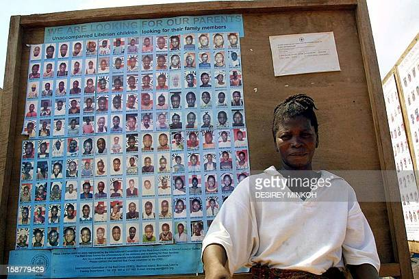 This recent file picture taken 14 May 2003 shows a Sierra Leonean refugee standing in front a Red Cross board displaying pictures of children looking...