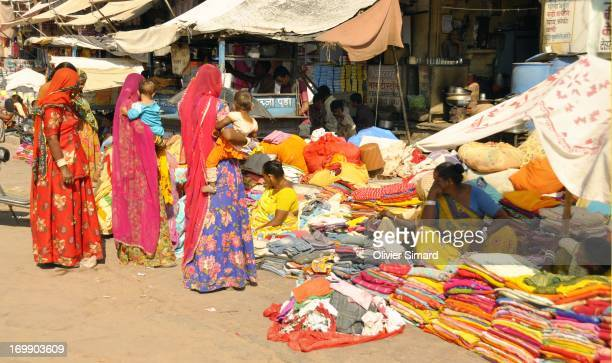 This scene takes place in Rajasthan, Jodhpur. In Sardar Bazaar, under the clock tower, the local women of Jodhpur are selling tissues and silks....