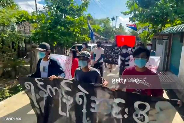 This screengrab from AFPTV video footage taken on May 11, 2021 shows protesters holding banners during a demonstration against the military coup in...