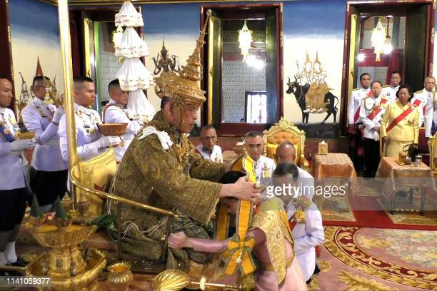 TOPSHOT This screengrab from Thai TV Pool video taken on May 4 2019 shows Thailand's King Maha Vajiralongkorn putting a sash on Queen Suthida after...