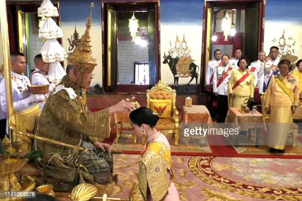 This screengrab from Thai TV Pool video taken on May 4 2019 shows Thailand's Princess Sirindhorn watch as Queen Suthida kneels in front of King Maha...