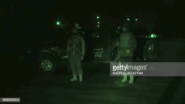 This screengrab made from an AFP video taken on January 20 2018 with the aid of a nightvision camera shows security forces standing guard in the...