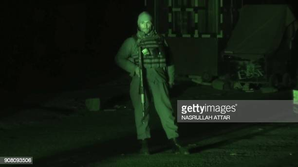 This screengrab made from an AFP video taken on January 20 2018 with the aid of a nightvision camera show a member of security forces standing guard...