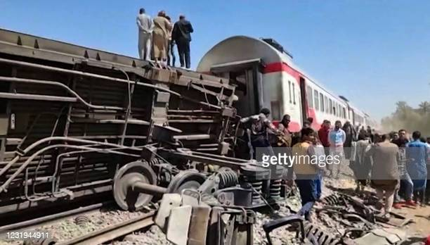 This screengrab provided by AFPTV ahows people gathered around the wreckage of two trains that collided in the Tahta district of Sohag province, some...