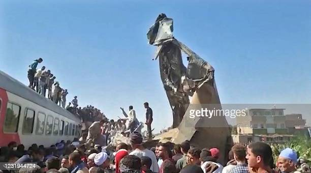 This screengrab provided by AFPTV shows people gathered around the wreckage of two trains that collided in the Tahta district of Sohag province, some...