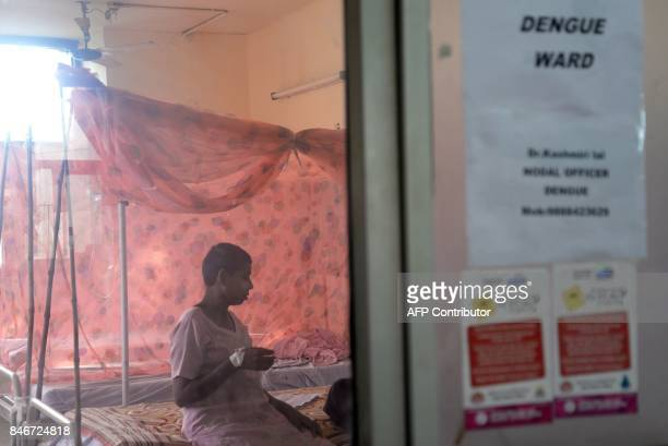 This September 12 2017 photograph shows an Indian woman who is suspected to have dengue sitting on a bed in a dengue ward in a government hospital in...