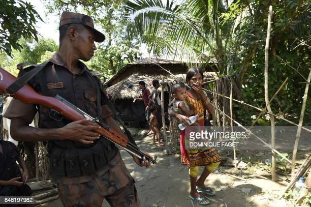 TOPSHOT This September 16 2017 photo shows a Bangladesh border guard looking at Rohingya refugees at the Jalpatoli refugee camp in the noman's land...