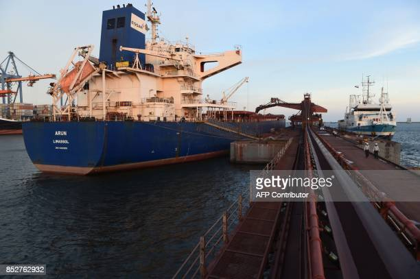 This September 21 2017 photo shows iron ore pellets on a conveyor belt being loaded onto a ship in the berthing area of the Vizag Terminal operated...
