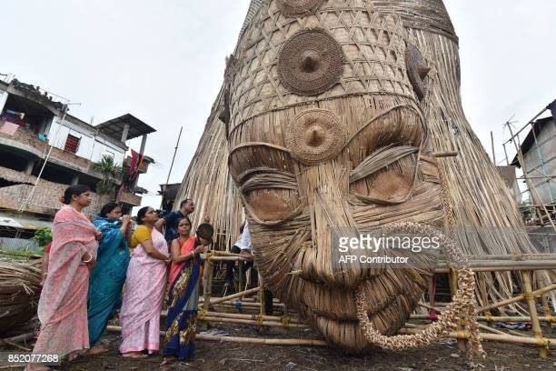 This September 22 2017 photo shows Indian Hindu devotees offering prayers to the head of a 100foot bamboo idol of the Hindu deity Durga in Guwahati...