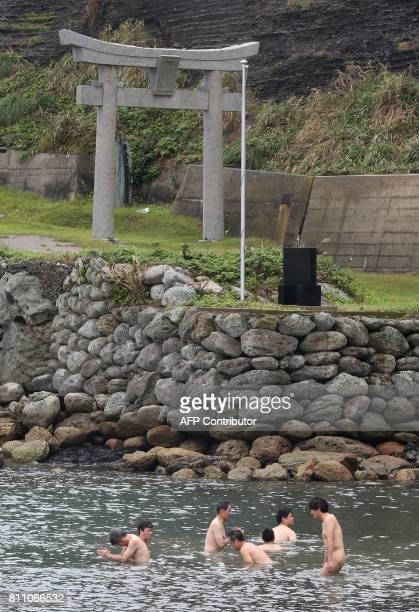This September 30 2016 picture shows devotees purifying themselves with sea water before entering Okinoshima island some 60 kilometres from Munakata...