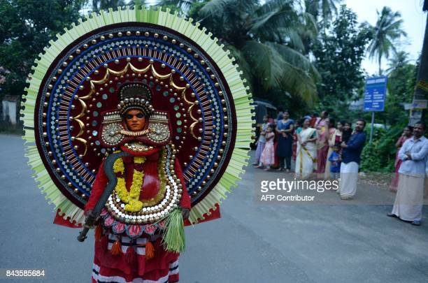 This September 6 2017 photo shows an Indian 'Theyyam' artist performing during the 'Kummati Kali' as part of the annual Onam festival celebrations in...