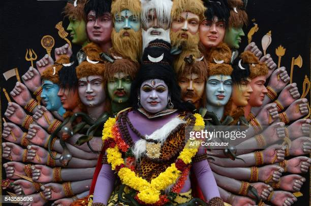 This September 6 2017 picture shows an Indian 'Theyyam' artist posing for a photograph while performing during the 'Kummati Kali' as part of the...