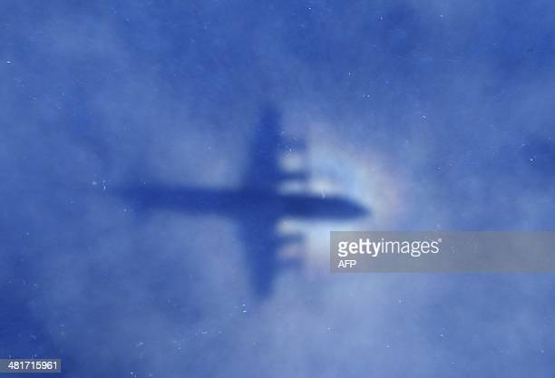 This shadow of a Royal New Zealand Air Force P3 Orion aircraft is seen on low cloud cover while it searches for missing Malaysia Airlines flight...