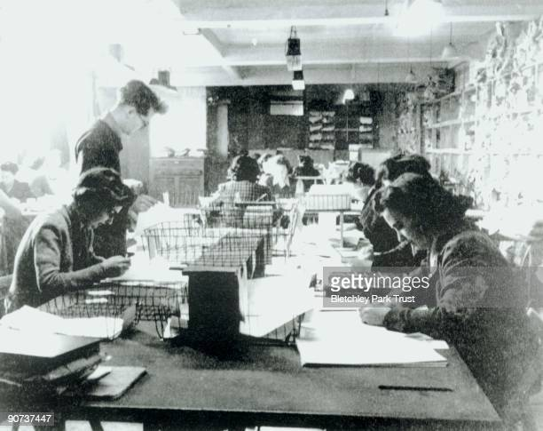 This shows one of the Hut 3 priority teams at Bletchley Park Buckinghamshire in which civilian and service personnel worked together at codebreaking...