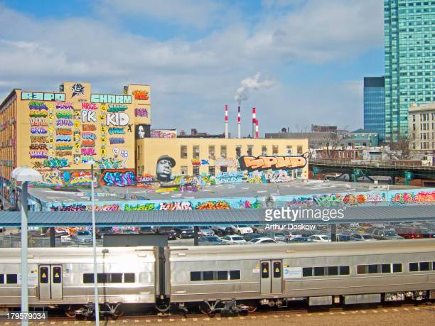 This shows the 5POINTZ urban art studio as seen from a train on the Flushing line of the New York City subway.