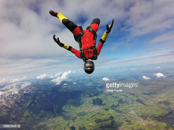This skydiver is flying high in the sky and is having fun by practise some free style exercise.