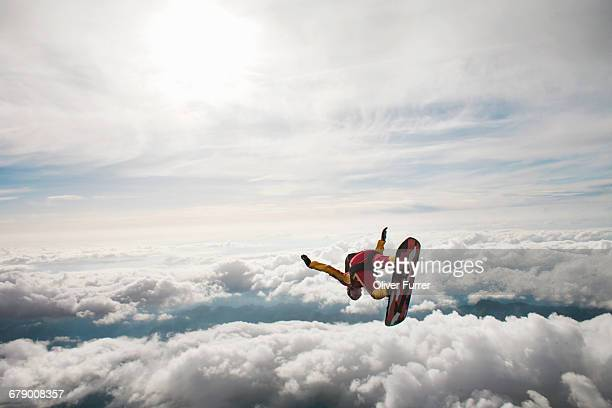 This skysurfer is riding his board over the clouds